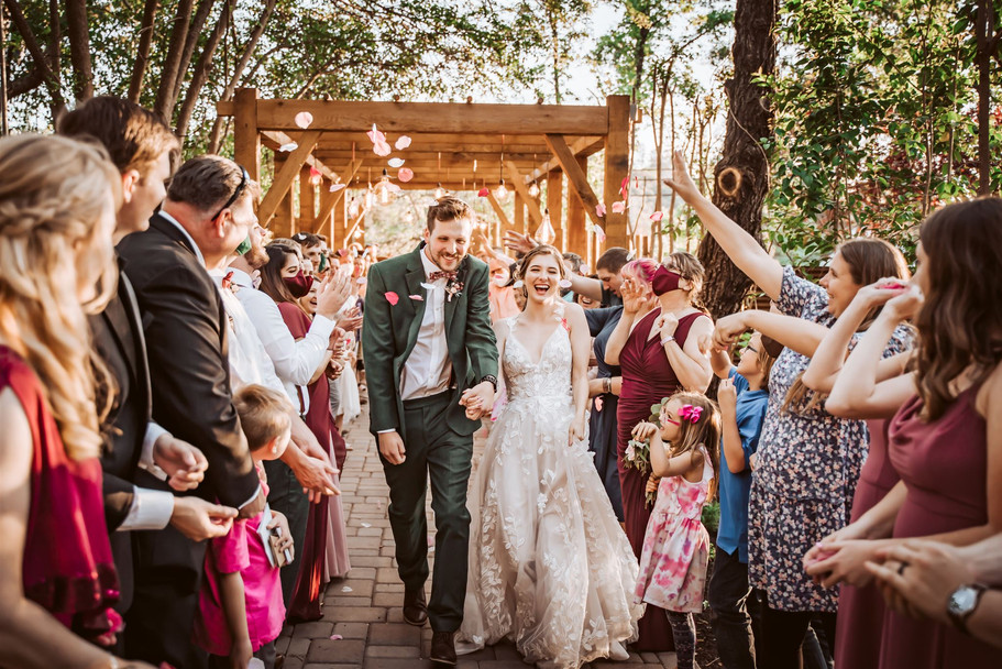 A wedding couple doing an exit with flowers being thrown in the air at Gardens at Sutter Creak, California