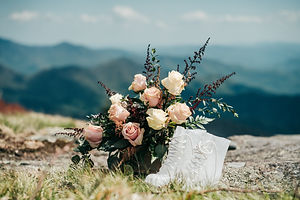A bouquet and clear wedding mountain boots overlooking the mountains of california