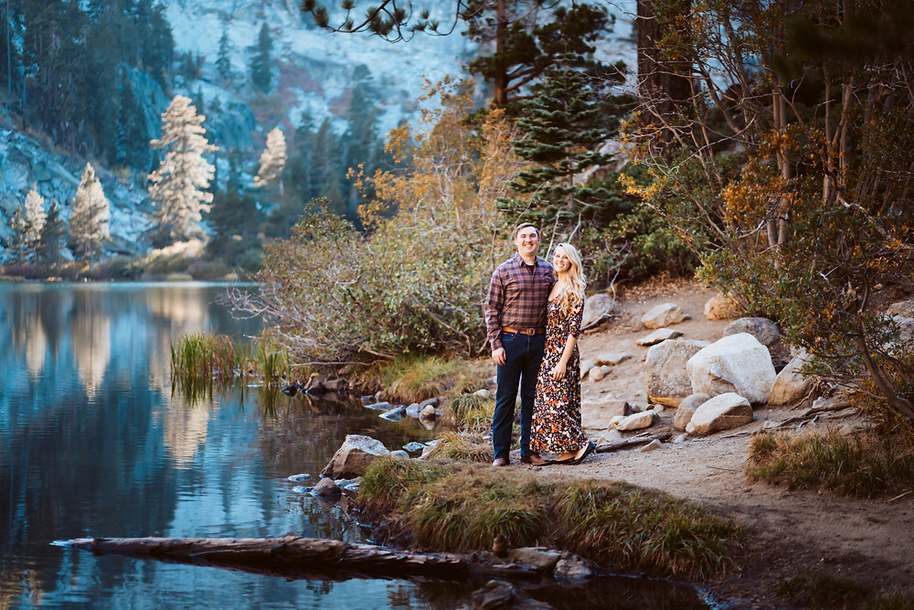 A couple standing on the edge of Lake Tahoe with a full reflection of the mountains in the lake with fall foilage