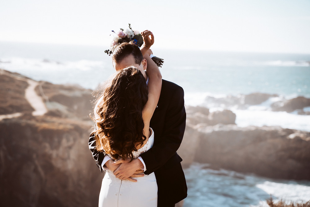 A first kiss from a bride and groom in Big Sur