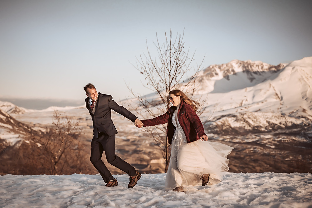 """A elopement couple running in the snow in Mt. St. Helens in there wedding attire and asked themselves """"Should we Elope?"""""""