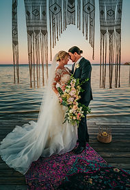 A wedding couple standing in front of a sunset on the ocean with a macrame decoration in the top and a beautiful rug on the deck