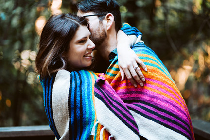 A couple wrapped in a mountain blanket in the forest during their mini moon