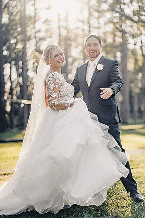 A bride and groom dancing in the sun.  The bride is wearing a very flowey lacey dress and the groom is wearing a grey tux