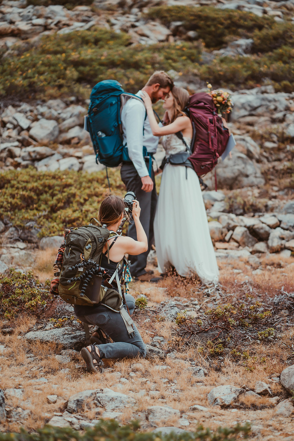 A photographer taking pictures of an elopement couple dressed in wedding attire and carrying their hiking backpacks