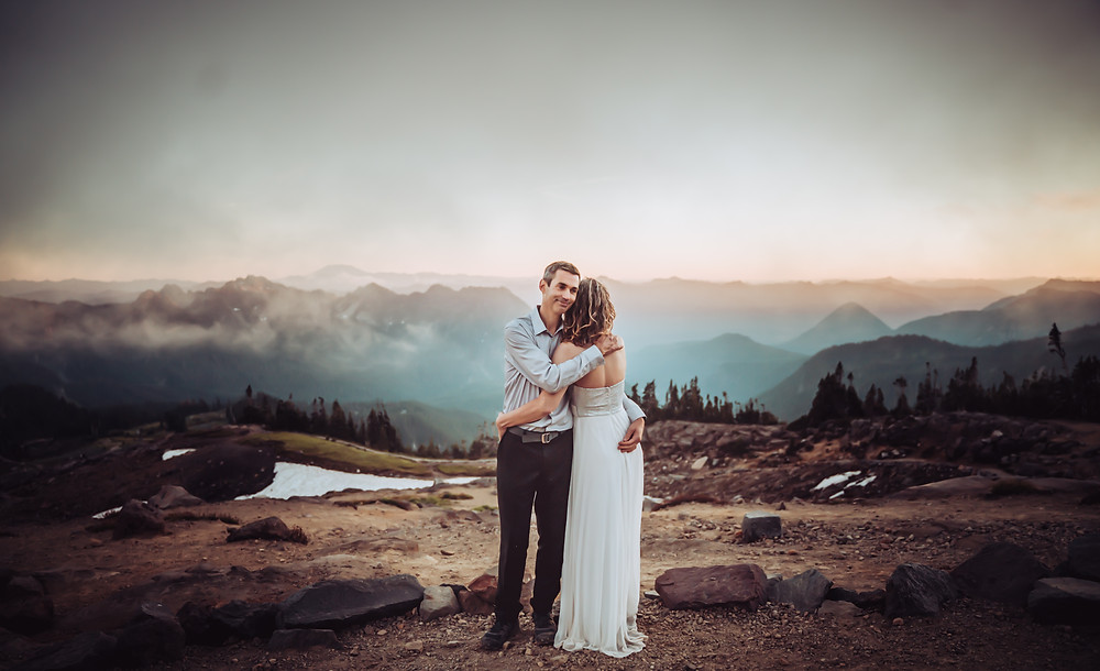 A bride and Groom hugging in front of a mountain sunset at Mount Rainier