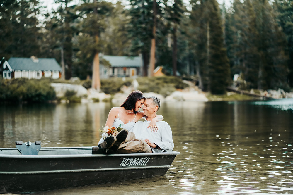 A bride sitting on the grooms lap in the back of a row boat in the middle of a lake with lake cabins in the backdrop.  Great elopement idea!  Photos of eloping in Lake Tahoe