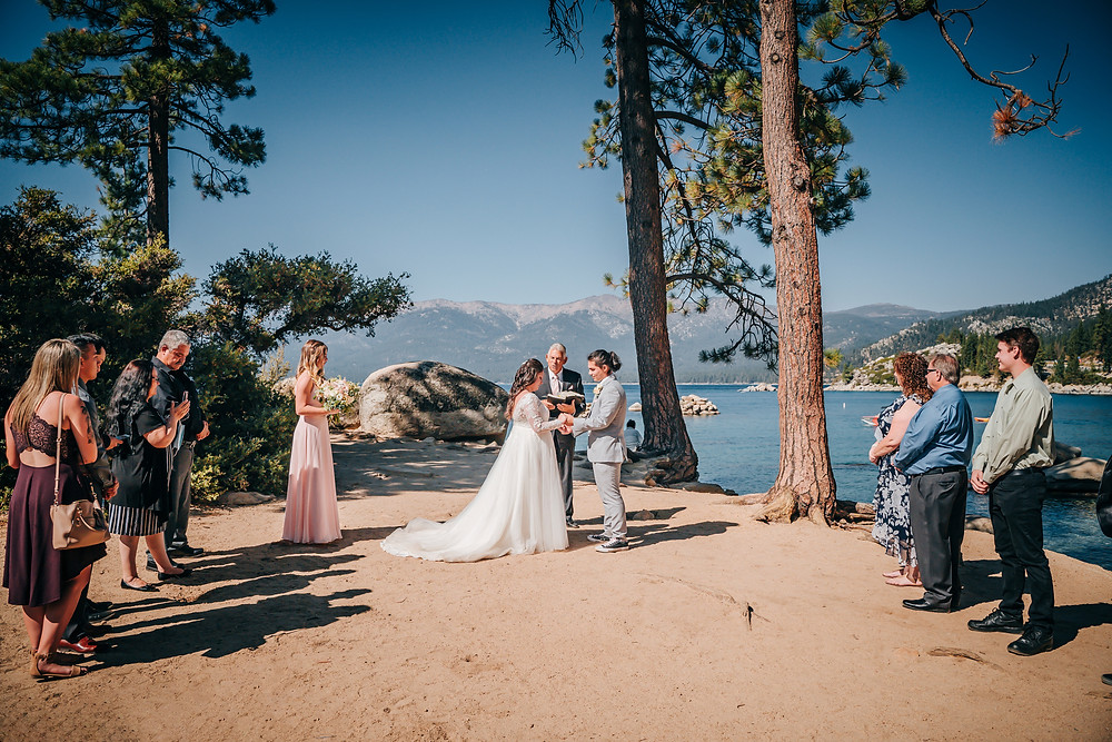 On of the best places to elope in lake tahoe is Sand Harbor and here is a couple getting married there right in front of the lake surrounded by a few family members