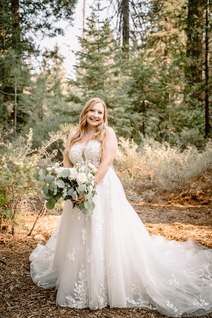 A beautiful bride standing in the forest on her wedding day