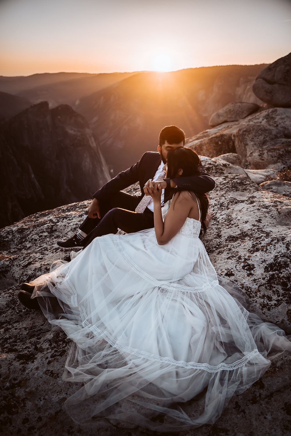 A wedding couple laying a rock at sunset in Yosemite during their California Elopement