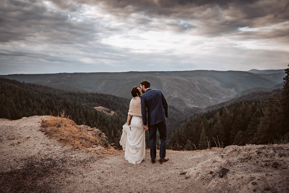 A wedding couple with their backs towards us kissing and looking out onto the Sierra Nevada Mountain Range outside of Nevada City, California