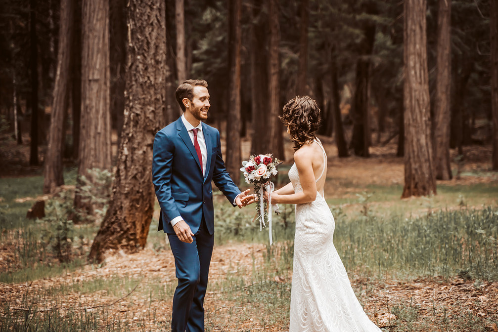 A groom seeing his bride for the first time for first look on their wedding day in the forest surrounded by trees.