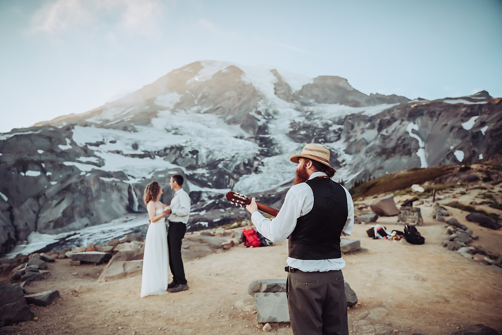 Bride and Groom doing their first dance behind a live musician playing a guitar with Mt. Rainier in the background