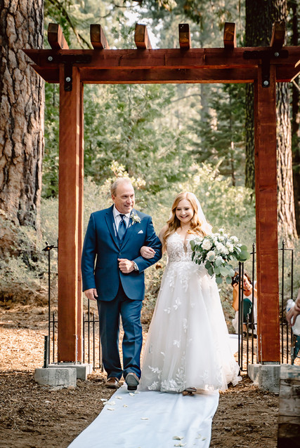 A dad walking his. bride down the aisle for her wedding day in the forest
