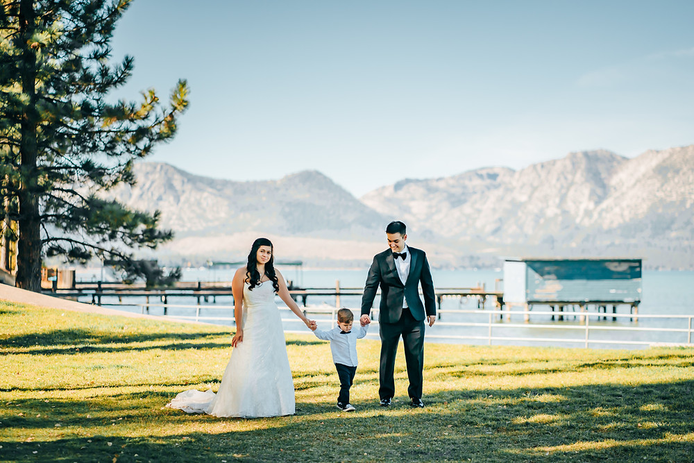 A bride and groom holding walking with their toddler son dressed in a cute little tux on the lawn of Thomas Ragan Memorial City Beach in Lake Tahoe for their elopement day