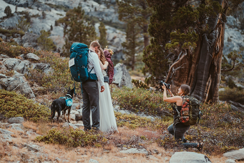 A photographer taking a photo of a adventure elopement couple wearing backpacks and in wedding gear and how to choose a wedding photographer