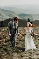 A bride and groom holding hands and smiling at each other walking in a field in the mountains