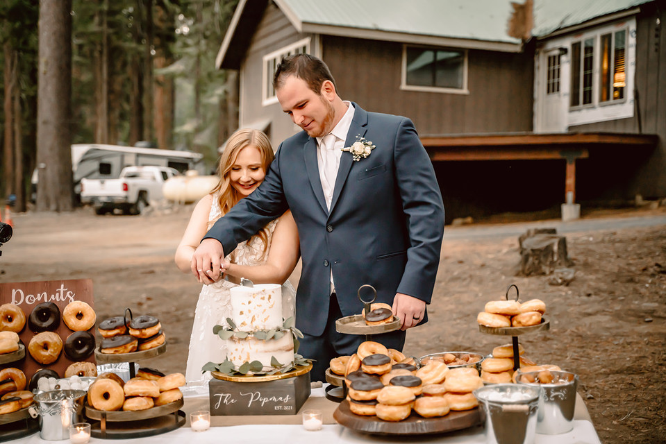 A bride and groom cutting their wedding cake at their outdoor wedding reception