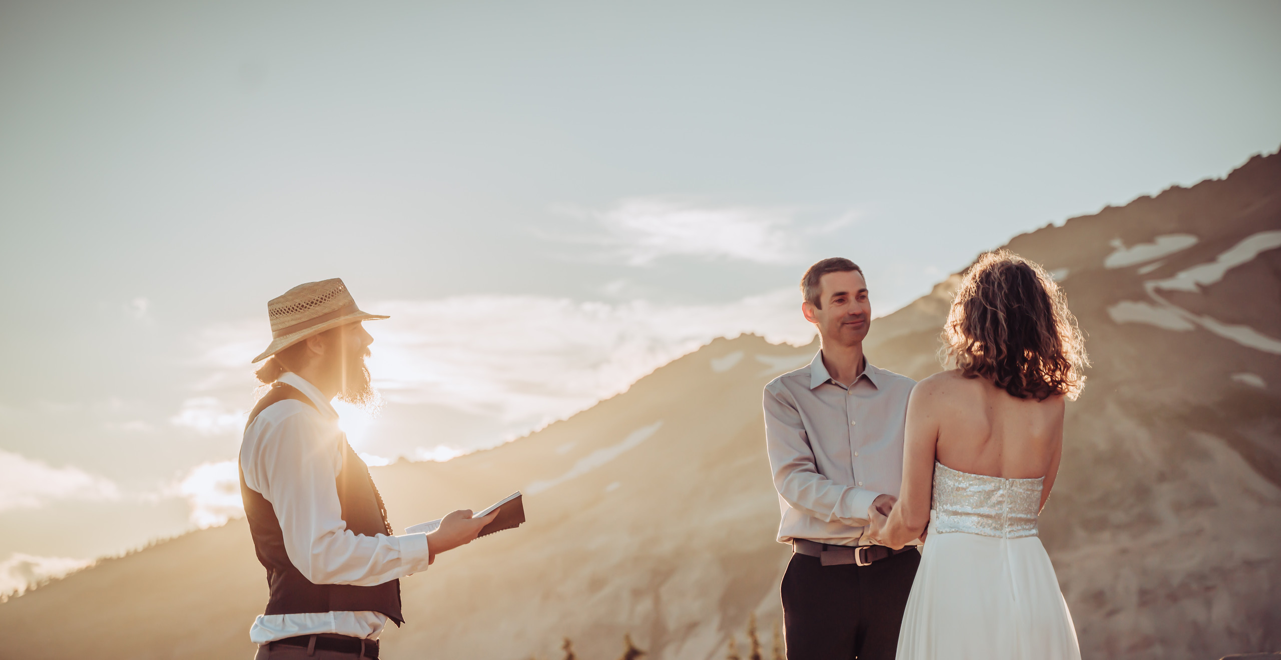 Officiant doing the vow ceremony in front of the bride and groom with Mt. Rainier as the backdrop