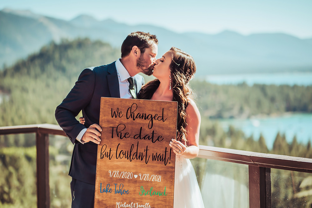 A bride and groom holding a sign that says we changed the date but couldn't wait to elope! they are standing in front of a backdrop of Lake Tahoe on their elopement day