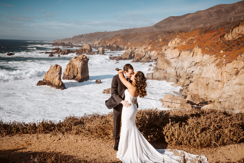 A bride and groom kissing on their elopement day in front of the cliffs of Big Sur