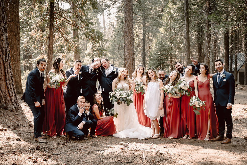 A full wedding party doing silly faces for their group photo on a wedding day at Camp Sylvester