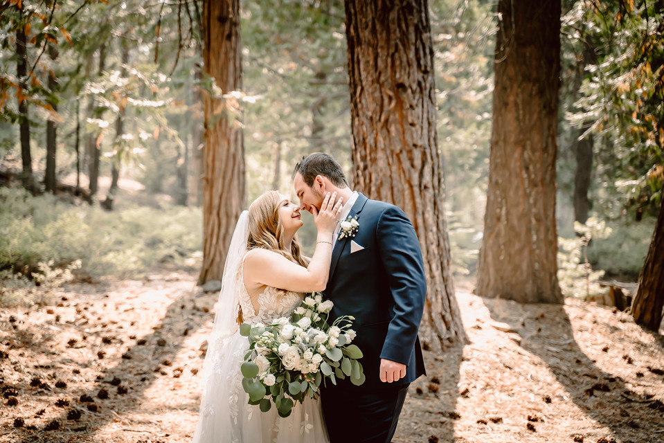 A bride and groom looking at each other in the forest on their wedding day in California