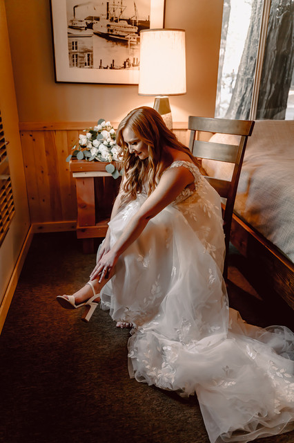 A bride putting on her shoes in her cabin at Camp Sylvester in Pinecrest California for her wedding day