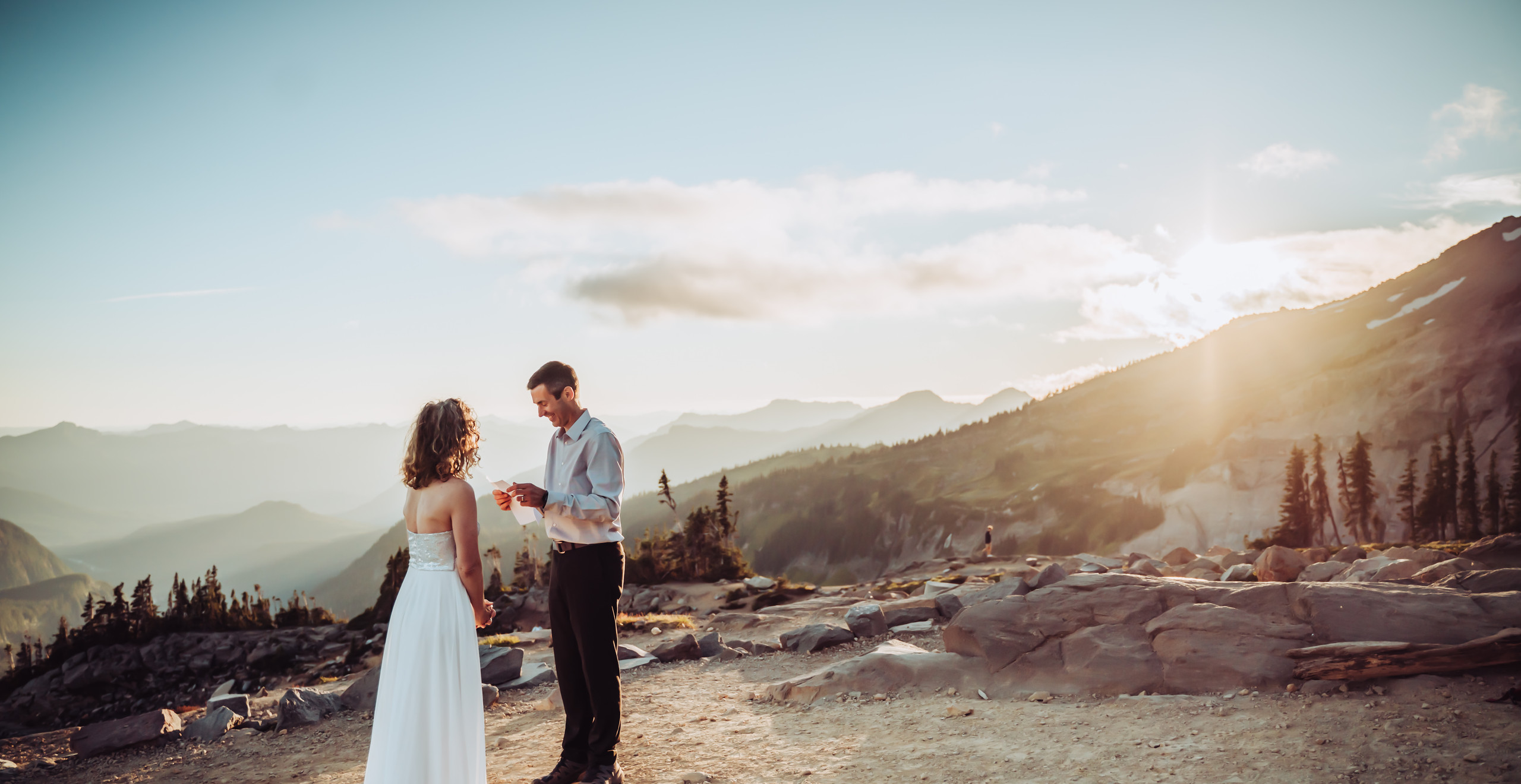 Groom reading his vows to his bride with Mt. Rainier in the background and a beautiful sunset