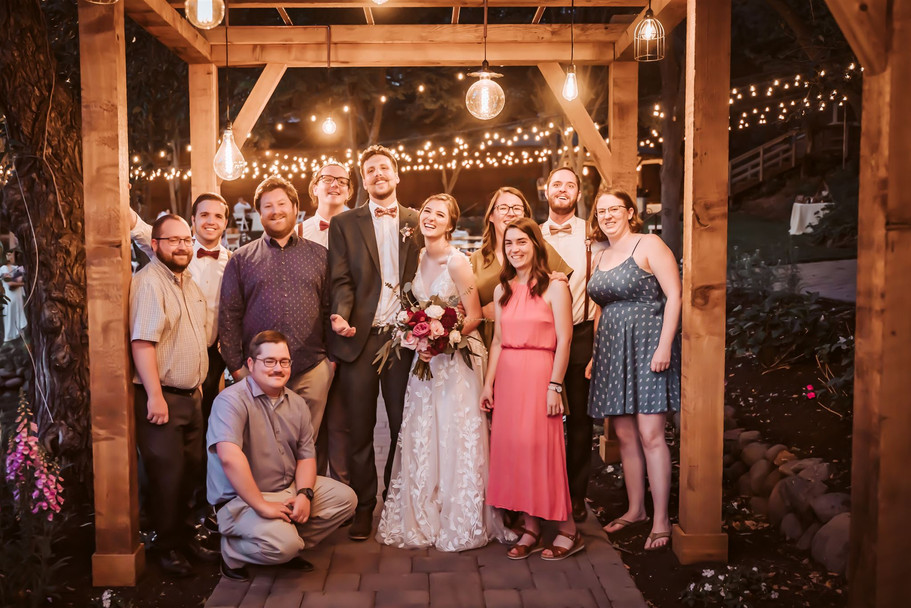 A wedding couple and their fiends under a canopy of twinkling lights