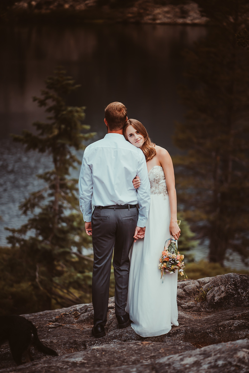 Bride leaning her head on her grooms shoulder standing on a rock an holding a bouquet.  The groom is looking out onto Eagle Lake in Lake Tahoe during a hiking elopement in Lake Tahoe