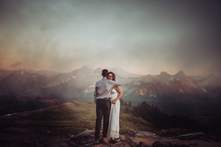 Bride and groom hugging with a mountain backdrop and the sunset and mountain fog from Mt. Rainier