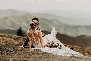 A bride sitting on her grooms lap wearing white clear hiking boots and looking out onto the mountains