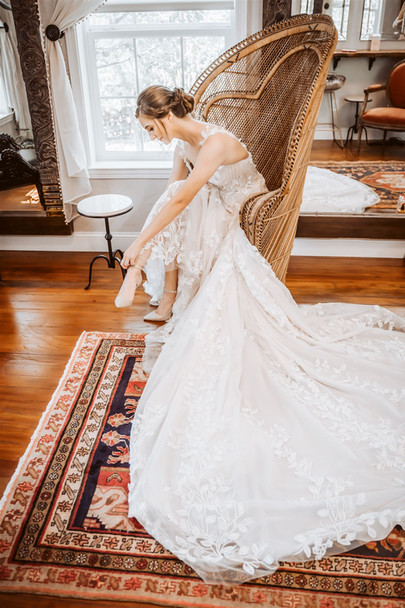 A bride putting her shoes on with a long train at Gardens at Sutter Creak