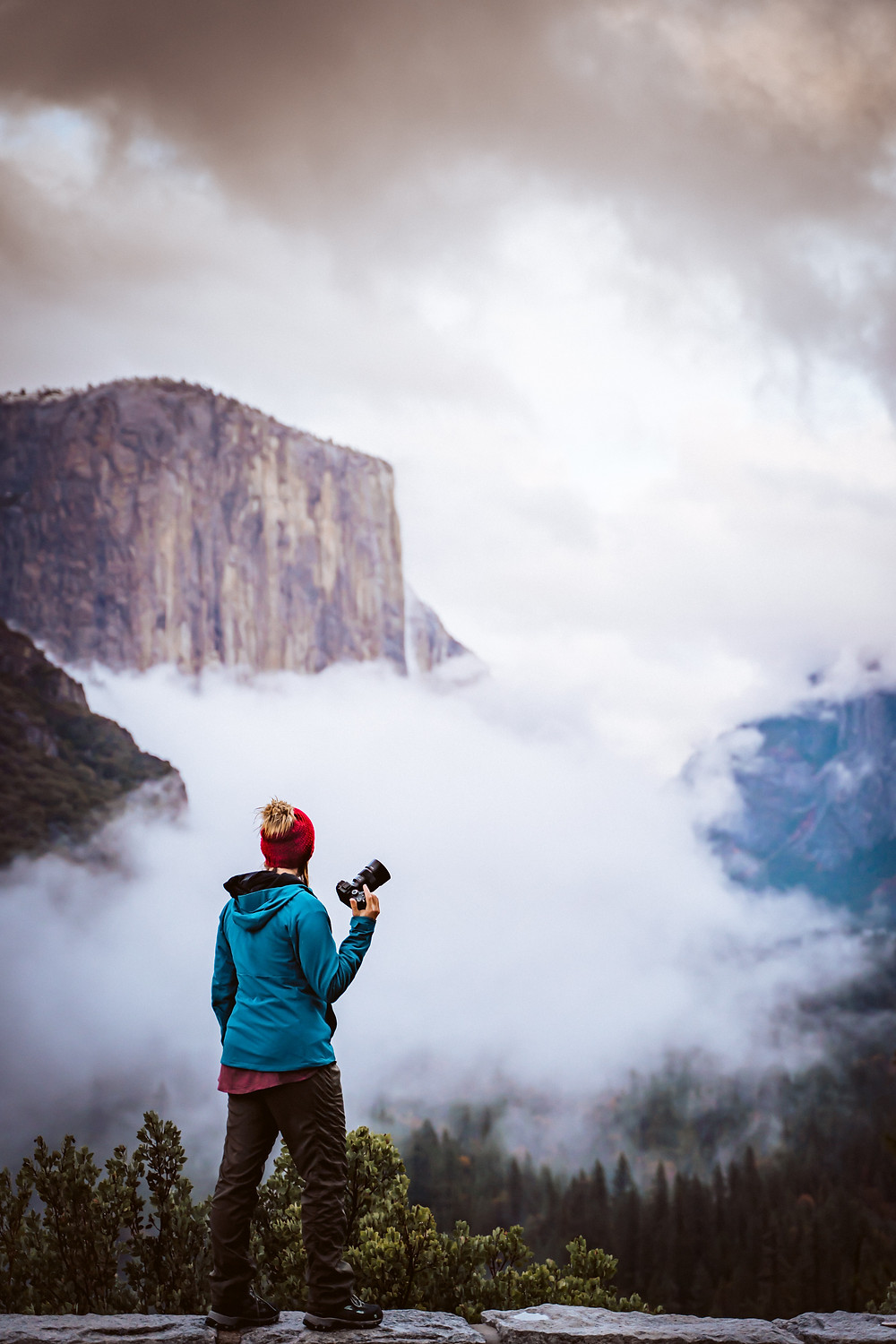 A girl holding a camera standing on the ledge and overlooking Yosemite Valley with Fog surrounding all around the base of El Capitan at Yosemite National Park