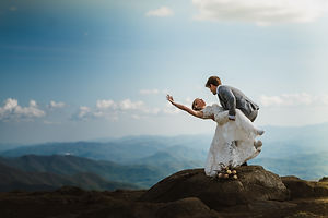 A groom dipping with his bride and standing on a large rock overlooking the mountains in california