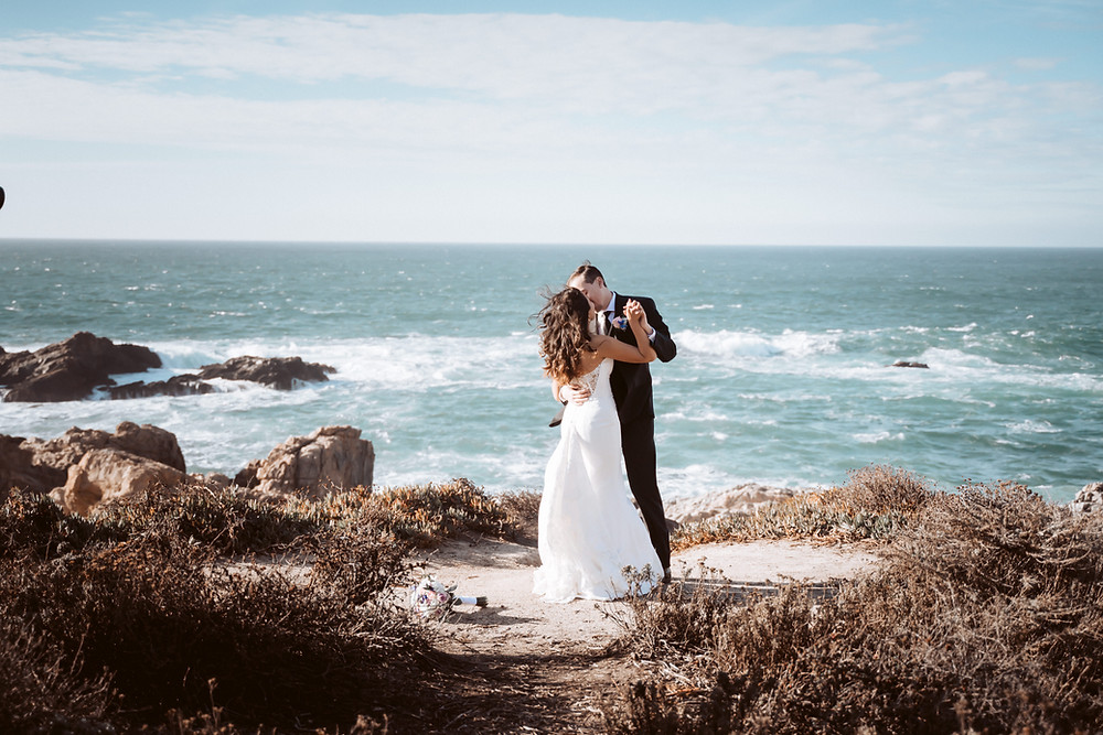 A bride and groom dancing on a cliff overlooking the ocean at Big Sur