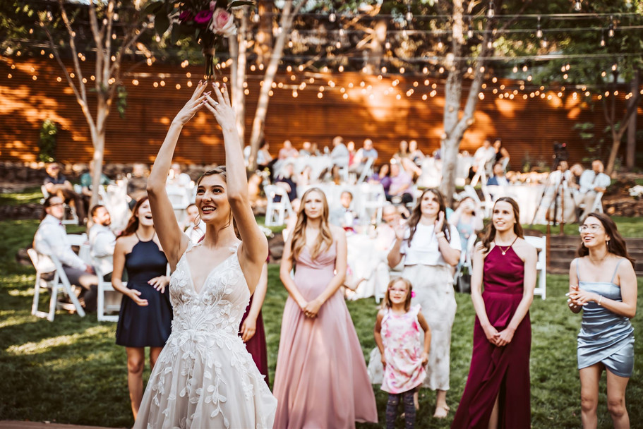 A bride throwing her bouquet under twinkling lights at the Gardens of Sutter Creek California
