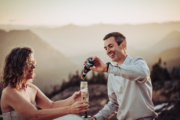 Bride and groom pouring a toast on top of the mountain with a sunset view of the mountain in the backdrop