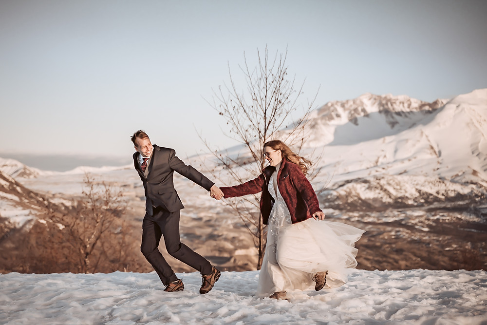 A groom running with his bride in front of Mt. St. Helens for their elopement
