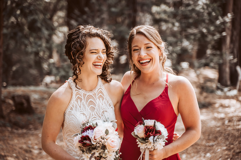 A bride and her bridesmaid laughing at the camera on her wedding day