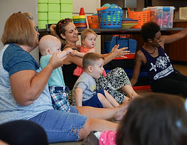 Caregivers and babies seated on the floor clapping hands