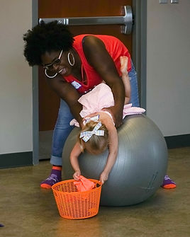 Toddler, being assisted by caregiver, lying over a large yoga ball, dropping a beanbag into a basket
