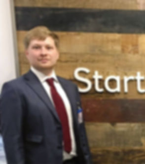 John J D Munn coach and consultant standing in front of start scale succeed sign
