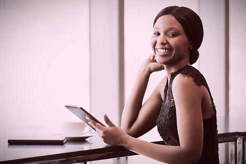 Pretty black woman holding an iPad looking toward you