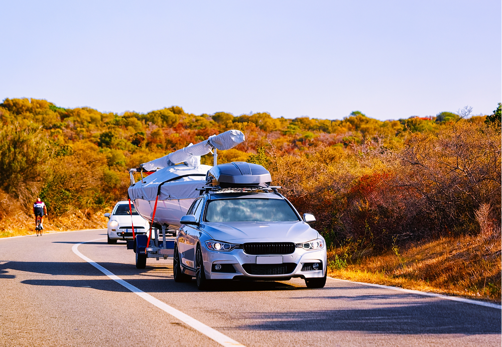 a car pulling a boat on a trailer, autumn