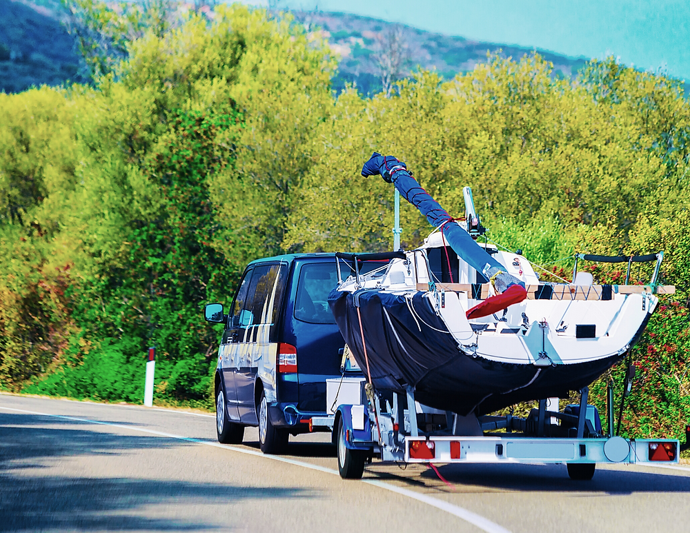 a car hauling a family-sized boat on the road using a boat trailer