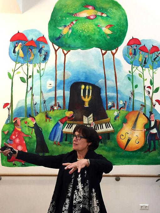 Künstlerin Juschi Seifried-  Otte erklärt die Wandmalerei