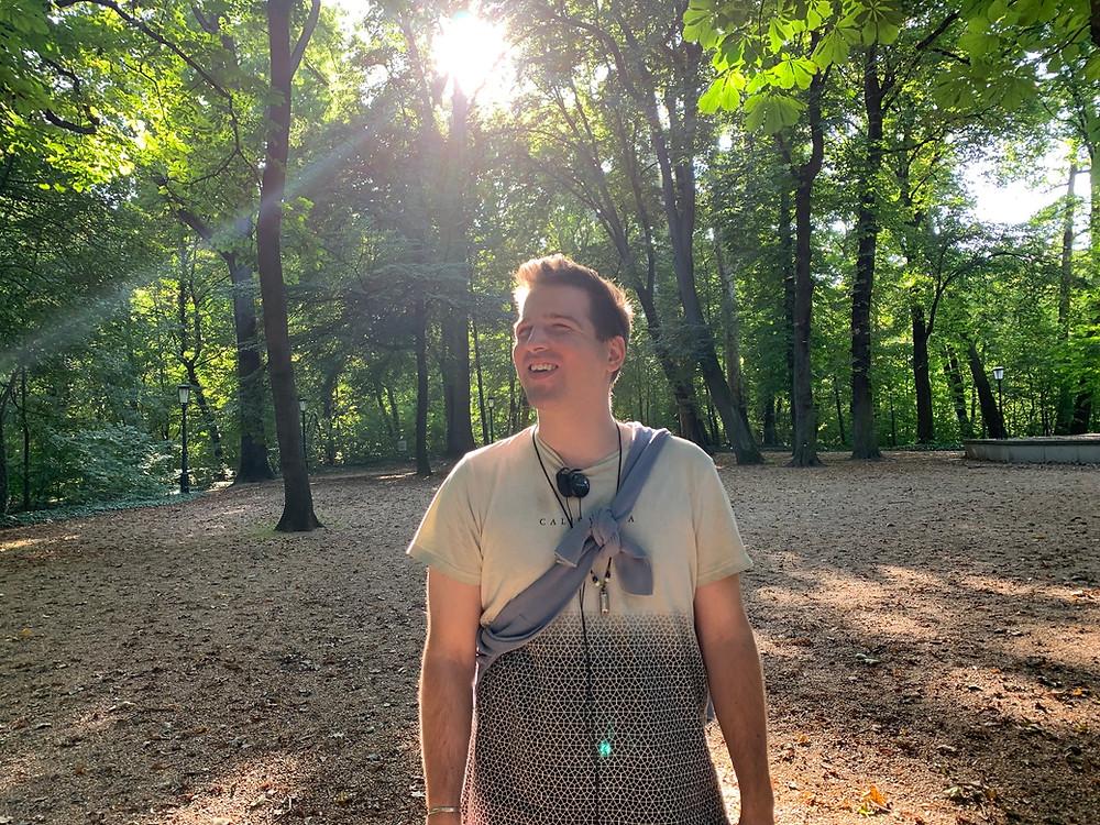 Juhász Tomi kirándul az erdőben. Süt a nap, zöldek a fák.