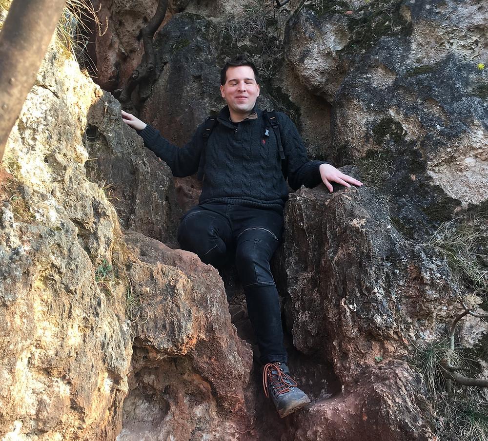 Juhász Tomi kirándul. Egy sziklán ül. Hátizsák van rajta és túrabakancs.